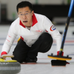Jason Chang throws a stone for the Hong Kong national curling team
