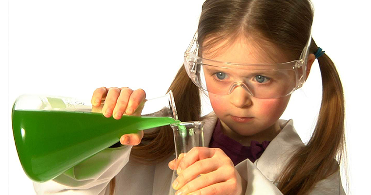 a girl in a lab coat doing a science experiment