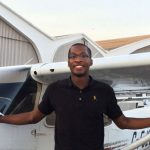 Alumnus Arthur Brown standing in front of a plane