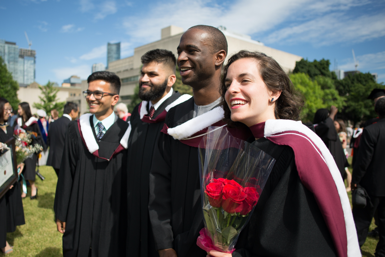 A group of students in graduation gowns stand on Front Campus on Convocation day.