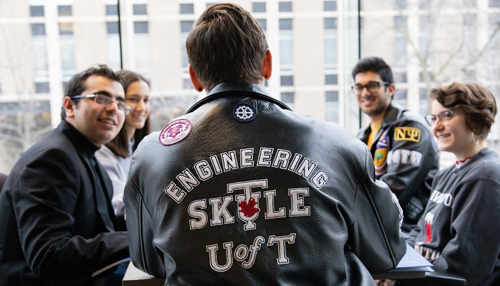 Students in SKULE jackets converse around a table in the Bahen Centre.